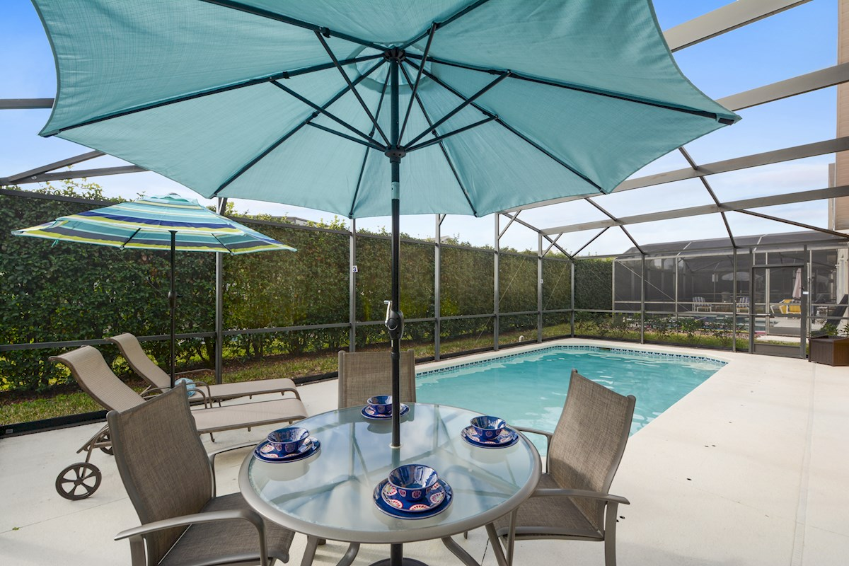 Enjoy a meal outdoors on the screened in pool deck.